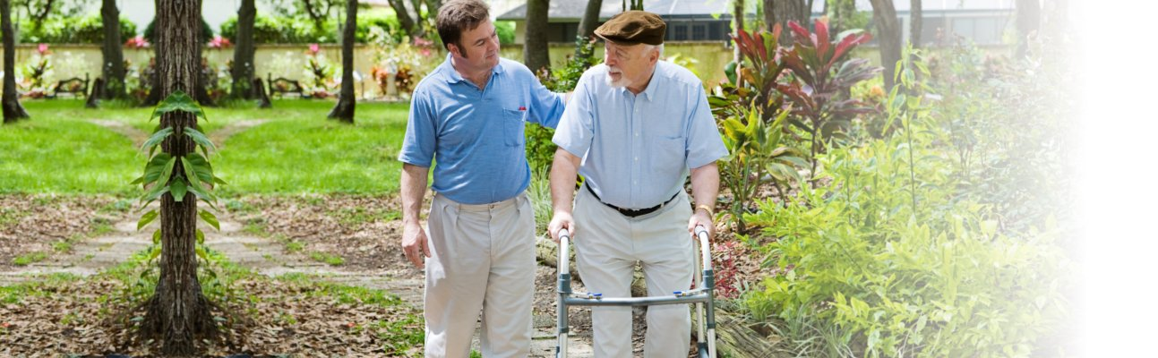 caregiver and old man strolling