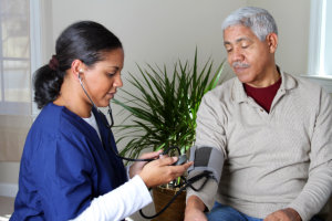 caregiver monitoring blood pressure of the senior man