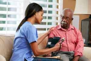 caregiver checking blood pressure of the senior man