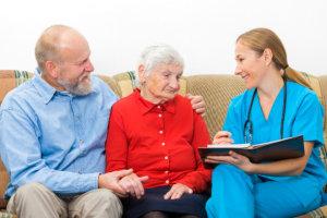 caregiver talking to senior couple